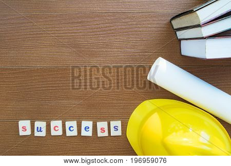Education success concept : Flat Lay. Safty Helmet Roll of drawing paper Textbooks on wooden table.