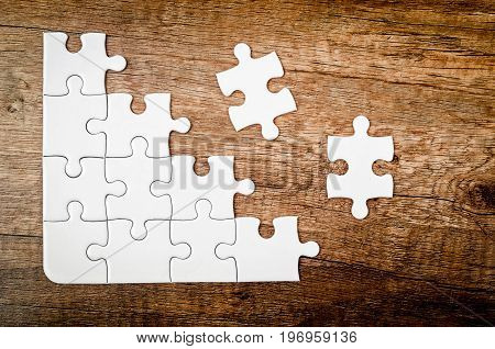 Placing missing piece of puzzle on wooden background