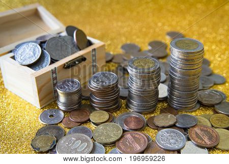 Stack of coins on golden glittering background pile of coins in small wooden chest with coins from various countries scattering around.