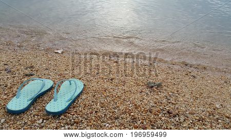 Take off your sandals. It's time for swimming. Blue sandals on sand beach.