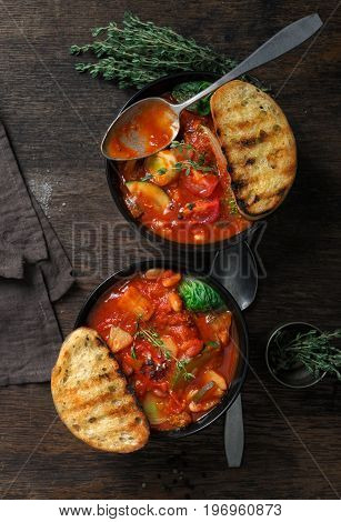 Two bowl of soup minestrone with seasonal vegetables on wooden table top view. Italian food