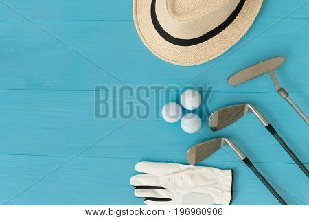 Golf concept : panama hat glove golf balls golf clubs on wooden table. Flat lay with copy space.