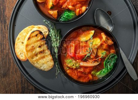 Two bowl of soup minestrone with seasonal vegetables on rustic wooden table close up top view. Italian food