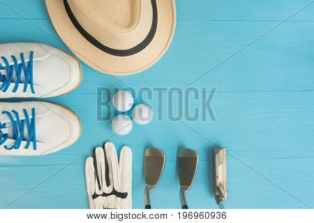 Golf concept : panama hat glove golf balls golf clubs golf shoes on wooden table. Flat lay with copy space.