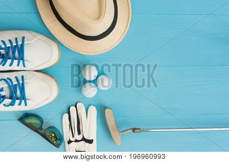 Golf concept : panama hat glove golf balls golf clubs golf shoes sun-glass on wooden table. Flat lay with copy space.
