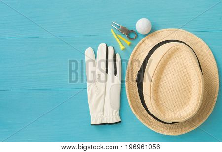 Golf concept : panama hat glove golf balls golf tees divot repair tool on wooden table. Flat lay with copy space.