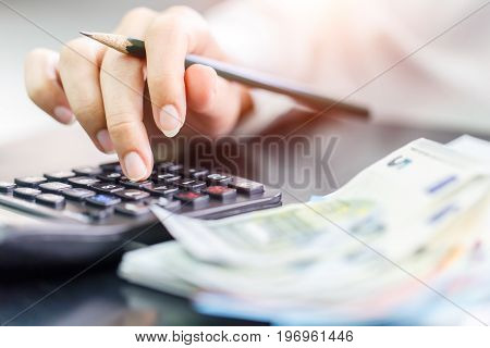 Close up right hand female using calculator in Euro banknotes background. Calculation at home
