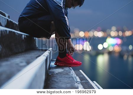 Asian Guy Tying Running Shoe, Preparing for Running for Dieting, with Bokeh light background