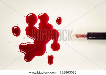 The A syringe with needle and blood.