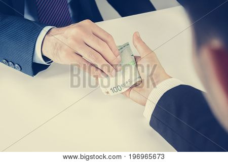 Businessman hands passing money Euro currency (EUR) bribery concept - vintage tone