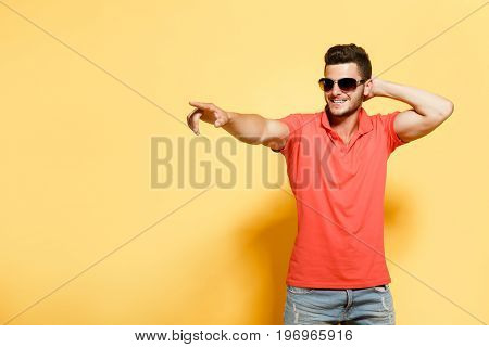 Young confident model in sunglasses and casual clothing posing on orange background pointing away.