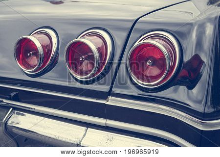 BERLIN - MAY 10 2015: Stoplight of a full-size car Chevrolet Impala (fourth generation). Stylization. Vintage toning. 28th Berlin-Brandenburg Oldtimer Day