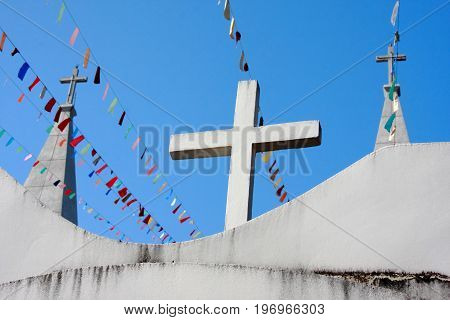 Three crosses on church roof with blue sky background.