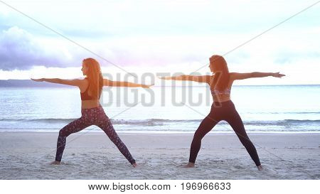 Young women doing yoga on a beach and stretching her body wearing a sports wear.