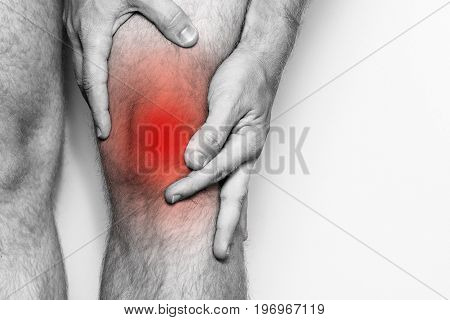 Acute pain in a knee joint close-up. Monochrome image isolated on a white background. Pain area of red color.