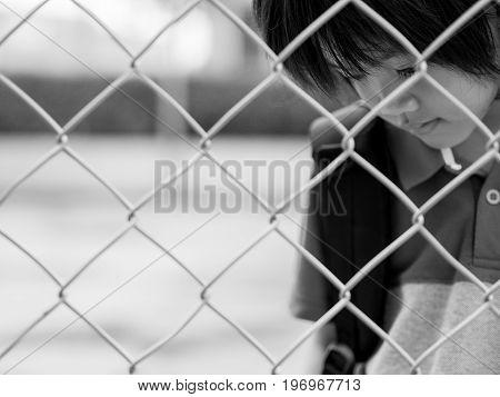 Black and white sad boy behind fence mesh netting. Emotions concept - sadness sorrow melancholy.