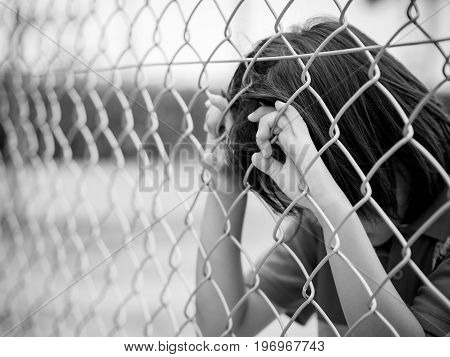 Portrait black and white sad boy behind fence mesh netting. Emotions concept - sadness sorrow melancholy.