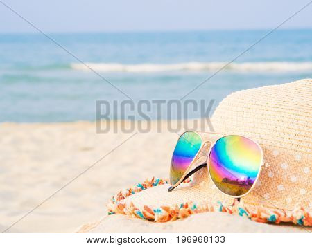 hat and sunglasses on the beach with sea backround Concept of summer traveling