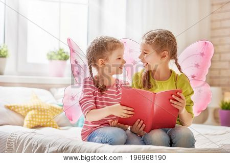 Two cute children girls reading a book on bed in room at home.