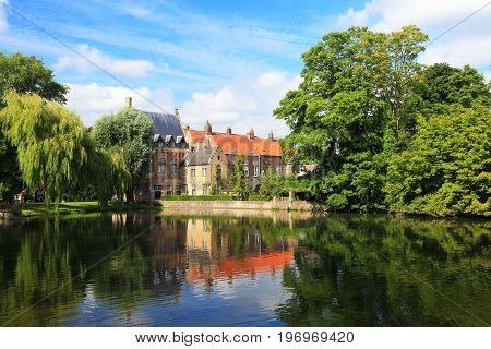 City view of Bruges. Bruges attractions in green trees reflected in water. Sunny summer day in Bruges.