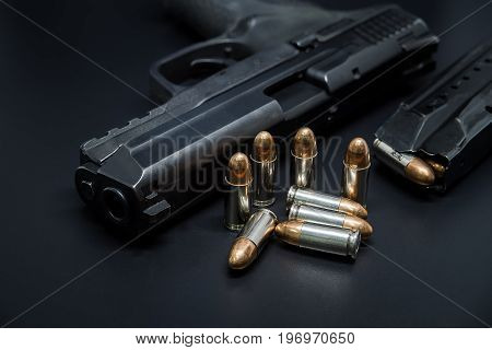 9 mm Pistol bullets and magazine on black background. Gun isolated