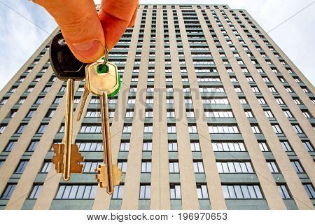 The keys to the apartment in the background of the facade of the house . Тhe concept of sales in the real estate market .