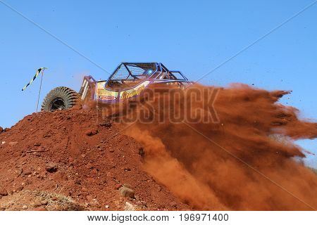Car Crossing Over Steep Hill, Kicking Up Sand And Stones.