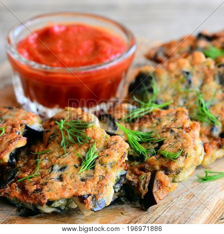 Eggplant burgers with dill and garlic on a wooden board. Red ketchup in a glass bowl. Easy and quick eggplant recipe. Vegetarian burgers idea. Closeup