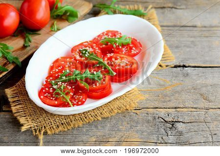 Light tomato and arugula salad. Delicious and dietary salad with tomatoes, arugula and sesame seeds on a white plate and a vintage wooden background with a copy empty space for text. Country style