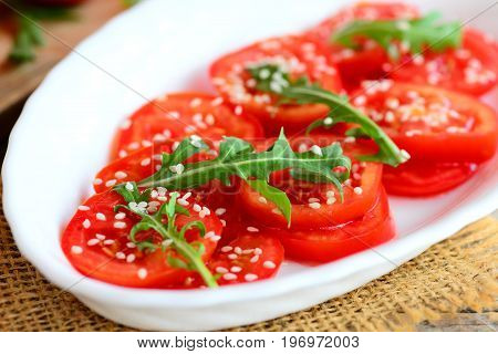 Tomato and arugula salad recipe. Home fresh tomatoes, arugula and sesame seeds salad on a white plate. Quick and healthy vegetarian salad recipe. Closeup