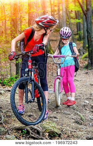 Bikes cycling family. Happy mother and daughter wearing helmet are cycling on bicycles into forest. Parenting. Color tone on shiny sunlight background.