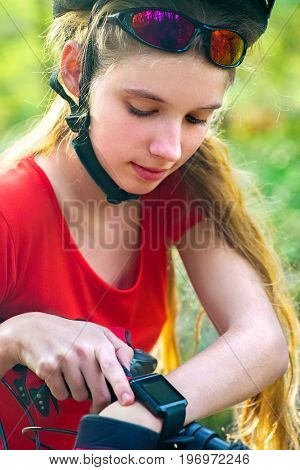 Woman traveling bicycle in summer park. Bicyclist girl watch on smart watch. Girl counts pulse after sport training. Sportswoman waiting for her friends. School trip.