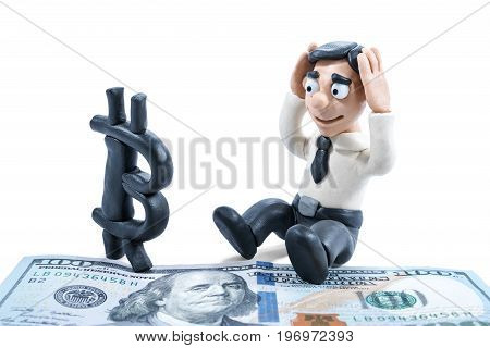 Conceptual photography. Plasticine businessman worries about bitcoin ousting dollar isolated on white background