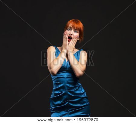 Young surprised woman showing by hands on a black background. Ideal for banners, registration forms, presentation, landings, presenting concept.