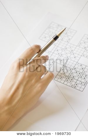 A hand holding a mechanical pen on a sudoku grid. poster