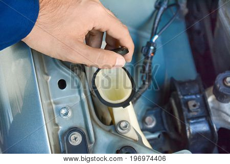 Hand opening car windscreen washer tank checking water level - hand focused