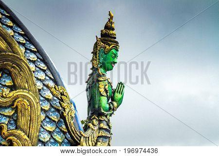 Chiang Rai Thailand - July 12 2017: Deva Statue Image Inside Wat Rong Sua Ten Or Blue Temple At Rain Clouds Background.