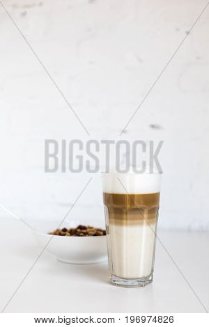 Glass Of Coffee Latte And Cornflakes In Bowl On White Table