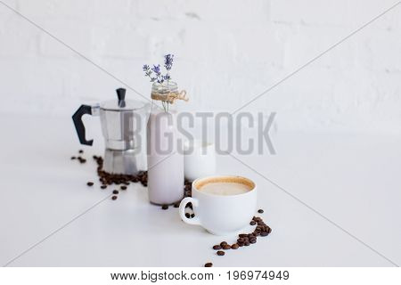 French Press, Cup Of Coffee, Milk Jar And Lavender Drink With Scattered Coffee Beans On White Table