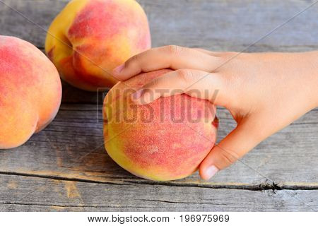 Small child takes a ripe peach. Sweet fresh peaches on a vintage wooden table. Delicious and healthy food for kids in summer