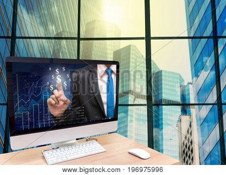 the computer on the wood table with Businessman point sign of money on the trading graph at the screen in front of the glass window over the blurred photo of cityscape background