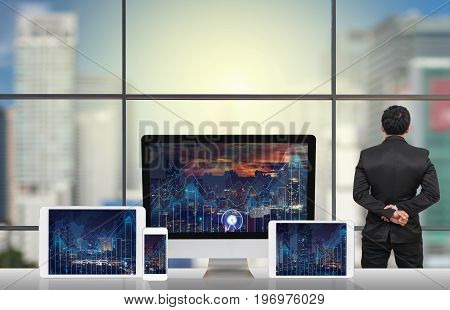 Back side of Businessman looking at city out off windows glass with Computer set show Trading graph on the cityscape and world map background on the table in meeting roomBusiness financial concept