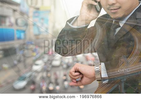 Double exposure of businessman looking his watch and calling phone call in rush hour with traffic jam backgroundbusiness transportation concept