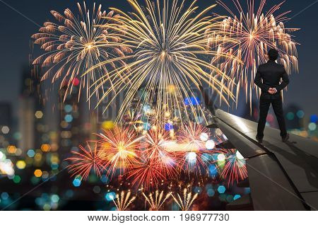 businessman standing on airplane wing which can see Fantastic festive colorful fireworks Challenge and success business concept