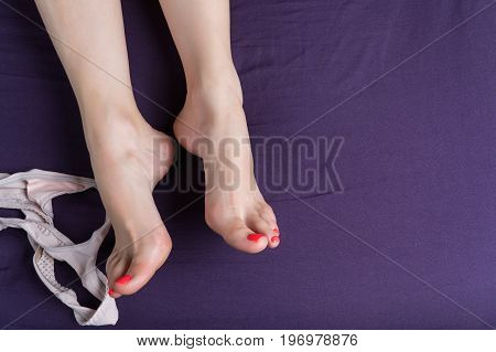 Female feet lie on a purple sheet with thong next to it.