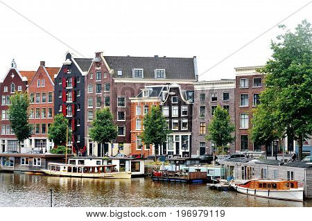 Amsterdam Holland Europe - scenic view of the canal boats and typical dutch buildings