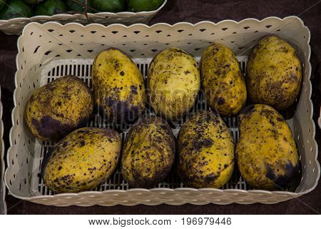 Nine ripened mangoes in a plastic tray