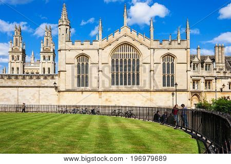 Oxford United Kingdom - June 20 2006: All Souls College (The Warden and the College of the Souls of All Faithful People Deceased in the University of Oxford) is a constituent college of the Oxford University. Students are talking at the fence of Radcliffe
