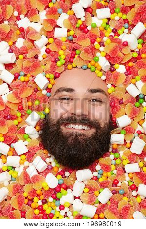 From above shot of bearded man lying in candies and smiling at camera