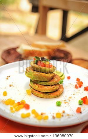 Vegetable fritters of zucchini on a wooden table in outdoor cafe